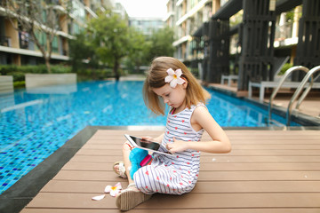 kid girl uses tablet sitting close to blue swimming pool wearing flower and hold toy. concept of new technologies travel, recreation or holiday family time on sunny day
