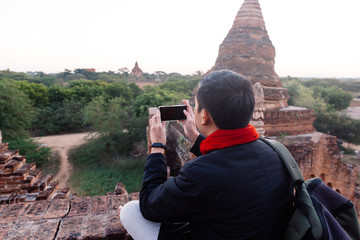 Young man taking a photo with mobile phone in temple stupa scene behind in Bagan, Myanmar.