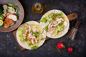 Healthy mexican tacos with baked chicken breast, cucumber, radish and lettuce. Flat lay. Top view