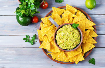 Guacamole avocado, lime, tomato, onion and cilantro, served with nachos - Traditional Mexican snack. Flat lay. Top view.