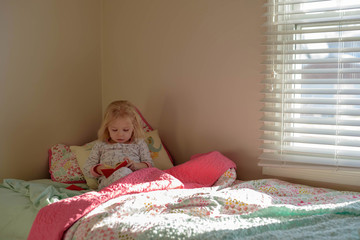 Little girl laying in big girl bed in the morning