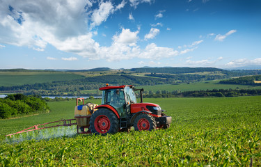 Fototapete - Red tractor and beautiful clouds.