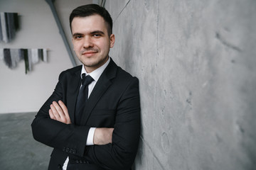 Portrait of a young successful man in a black suit against a gray concrete wall in loft style. Proud look.