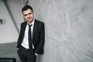 Portrait of a young attractive man in a black jacket and tie against a gray wall in the loft style. Young businessmen or freelancer.