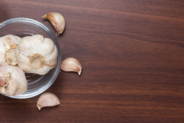 Garlic scattered on a wooden table with peel and inscription with space for text Top view