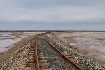 old rusty railroad tracks on gravel embankment at salt mining site  Lake Baskunchak, Astrakhan region, Russia