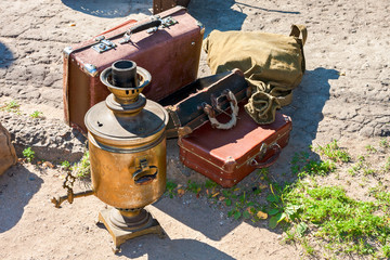 Vintage travel luggage with old suitcases and copper samovar in sunny day
