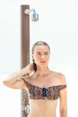 Beautiful woman is washing under the shower on the beach