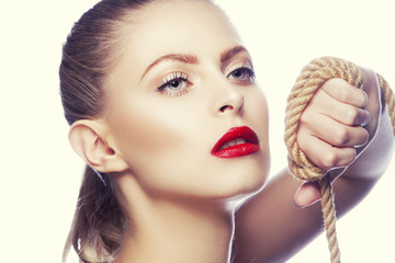 Beauty girl face with bright salon makeup and clean skin with rope on hands