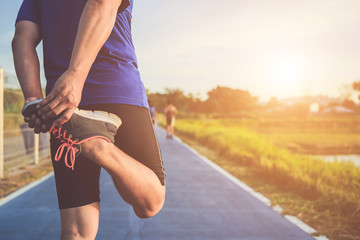 Man workout and wellness concept : Asian runner warm up his body before start running on road in the park. Focus on shoe. Shot in morning time, sunlight and warm effect with copy space  Wall mural