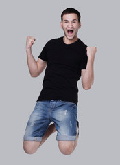 Excited  young man jumping isolated over a white background