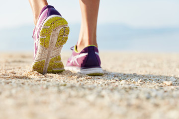Cropped shot of female`s legs in purple training shoes stands at sandy beach on coastline, being in motion, has workout or morning exercises in open air, participtaes in marathon or competition