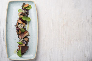 Portobello mushrooms with black lentils in rectangular plate, top view and copy space