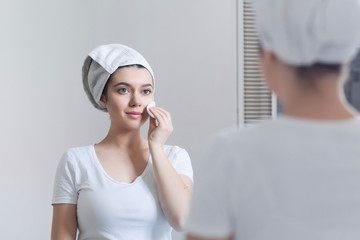Young 25-year-old woman caring of her skin on the face, standing near mirror in the bathroom, uses a cotton disc and tones the face. Girl moisturizes the skin after a shower.