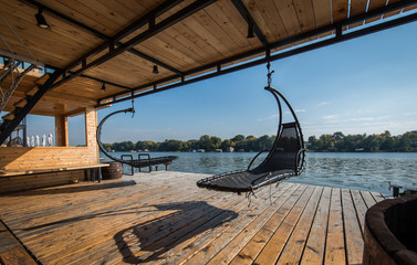 Outdoor hammocks on terrace of house by river