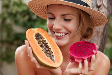 Close up shot of happy female with cheerful expression motivates you eat healthy food, holds papaya and dragon fruit, going to make fruit salad, tastes for first time exotic yield in tropical country