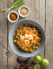 Thai noodles Stir fry with prawn, tofu and vegetables. Famuose and delicious street food in thailand. Flat lay. From top view on wood background