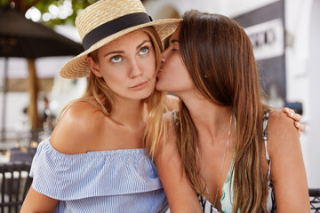 Portrait of fashionable young females lesbians have passionate kiss, have good relationships, demonstrate true love, recreat together against outdoor cafe interior. Homosexual relations concept