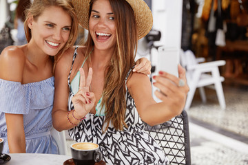 Happy beautiful two young women pose at camera of modern cell phone, make selfie, have positive and joyful expressions, drink tasty coffee at cafeteria. Joyful best friends enjoy togetherness