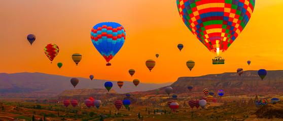 Hot air balloons sunrise landing in a mountain