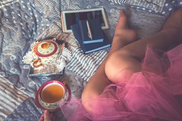 girl in a pink skirt a pack on a bed with a cup of tea and notepads and a tablet, legs close-up, a concept of modern fashion and trends in the fashion