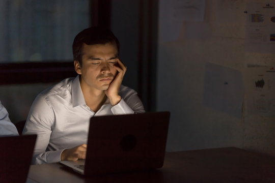 Tired and sleepy businessman closing eyes while working with team till late night in low light from laptop screen with blurred lighting bokeh background.Overtime hours concept.