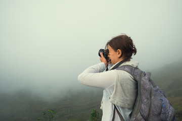 Caucasian woman making photo standing on the top of mountain. It is very cloudy but she tries to shoot.