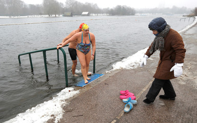 Swimmers emerge from the Serpentine lake in Hyde Park in London