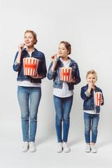 smiling family in similar denim clothing eating popcorn isolated on grey