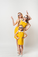 beautiful posing mother and daughters in similar retro style yellow dresses on white
