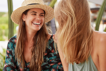 Pretty lovely woman with cheerful expression, wears summer hat and blouse, looks happily at her girlfriend who stands back to camera, have pleasant talk between each other. People and relatioship