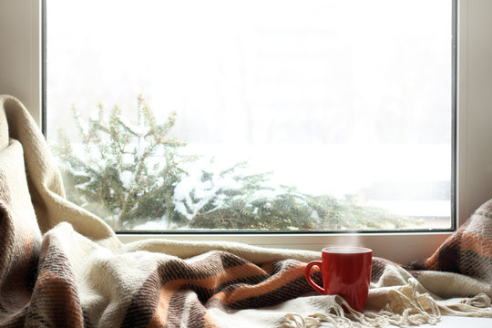 cozy home atmosphere in the winter/ red mug of hot drink on a windowsill with a warm blanket, when behind is window is snow