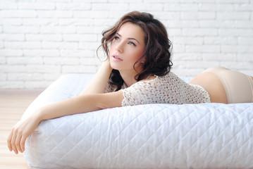Девушка в белом интерьере. Девушка на кровати отдыхает дома. Девушка на матрасе. Кровать на полу. Белый кирпич в интерьере. Утро милой девушки. Светлый интерьер дома.