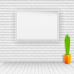 White brick wall with white wooden floor. On the wall hangs an empty white picture. On the floor is a pot with green plant