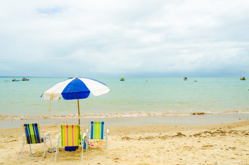 Isolated beach with three colorful beach chairs and a blue and white umbrella. A small wave breaks in the sand and some boats are in the sea. Cloudy sky.