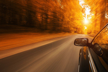 Close up of a car speeding on the empty, autum road with copy space Fototapete