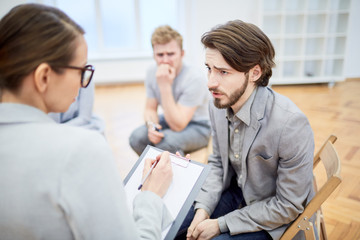 Troubled young businessman explaining his problem to counselor during group session