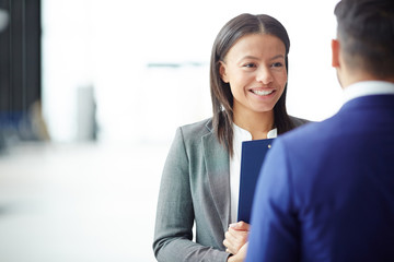 Young employee with toothy smile listening to her business partner during talk