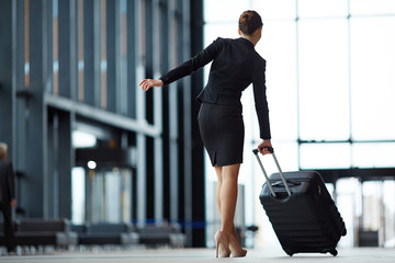 Back view of elegant businesswoman in suit and high-heeled shoes pushing her suitcase before her in airport
