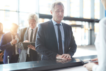 Mature traveler standing by check-in counter and answering questions of administrator
