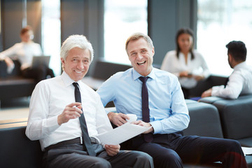 Two laughing mature businessmen looking at camera while having meeting in airport lounge