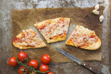 Slice of Margherita pizza on rustic background