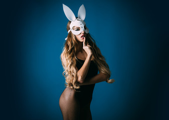 Easter bunny girl. Hot and sexy fashion portrait girl in bunny mask. Beautiful seductive woman in sexy lingerie and in bunny mask shows sign shh. Sexy blonde bunny girl.