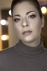 Cute beautiful young caucasian brunette woman with evening make up in casual outfit posing with neutral emotions. Mirror with lights on a background. Close up of a fresh clean face skin. Copy space