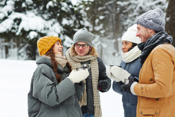 Group of happy young friends having hot drinks and talking while enjoying winter day in the forest