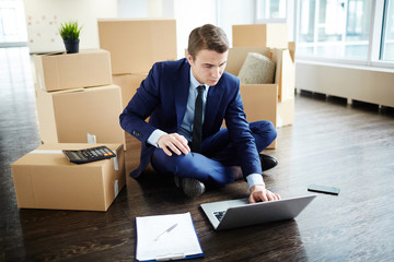 Busy young manager in suit sitting on the floor of new office among boxes and browsing in the net