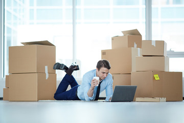Relaxed businessman with glass of coffee lying on the floor of new office with laptop in front and packed boxes near by