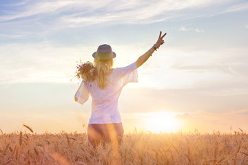 girl enjoying nature on the field. Beauty girl in the open air, raising her hands with a bouquet in the rays of sunlight. Beautiful teenage girl model on a wheat field. Concept free happy woman