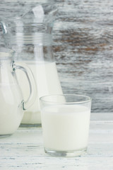 Milk in the glass jugs, white wooden background