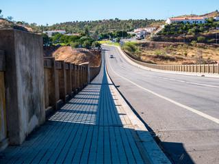 Auto auf einer Brücke mit Schatten vom geläunder